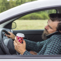 Driver holding coffee and talking on cell