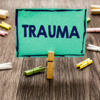 Green sign that reads trauma - to highlight that traumatic injury can result in conditions such as Complex Regional Pain Syndrome (CPRS)