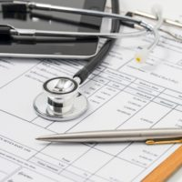 Stethoscope on medical billing statement on table, all text is a